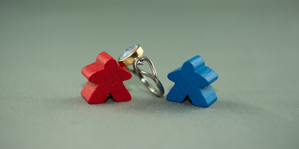 Red meeple beside blue meeple, with fire opal engagement ring between them, a heart shape on the side band. Typically I play red, and he plays blue. Oh yeah, ad that's my ring!! <3